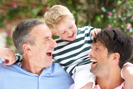 Grandfather And Father Giving Grandson Ride On Shoulders